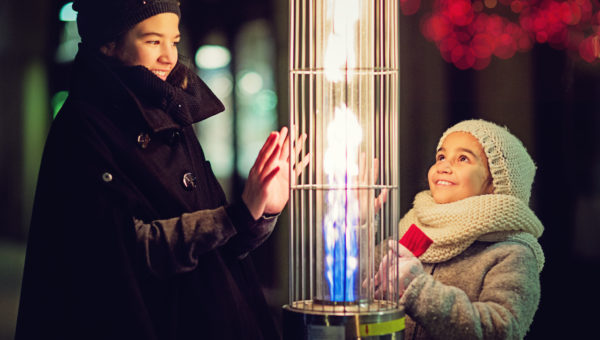 Girls are warming their hands on the restaurant gas heater in the cold winter night